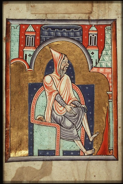 February: a man warming himself at a fire
