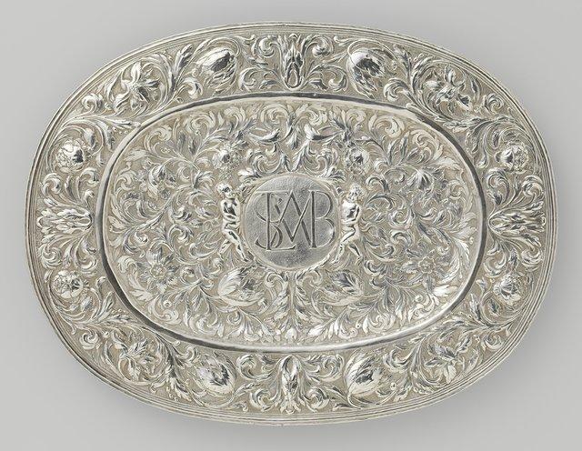 Lampetschaal, ovaal en geheel gedreven met bloemranken, met in het midden van de rand een medaillon met monogram, bestaande uit de letters SLMVB