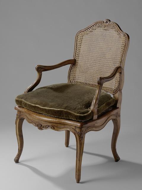 Armstoel met rieten zitting en rug en met een los kussen. Overhoeks geplaatste S-vormige poten en geschulpte onderregel.