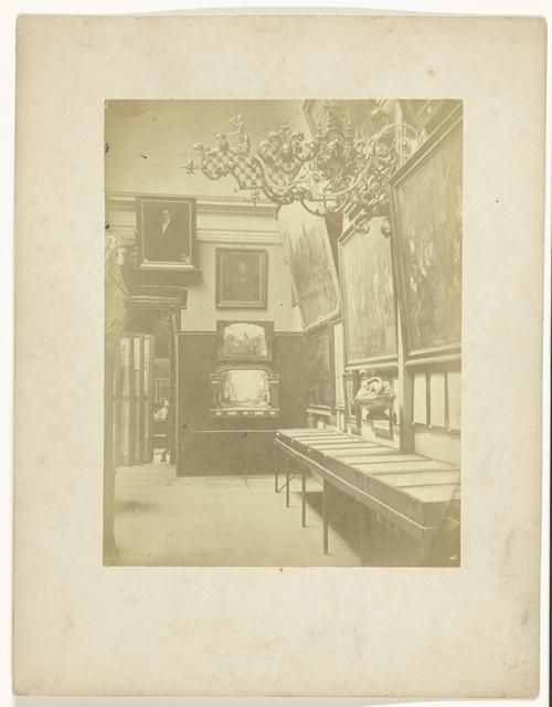 Gezicht in zaal E van de Historische Tentoonstelling Amsterdam 1876, met het uithangteken met attributen van het smidsgilde
