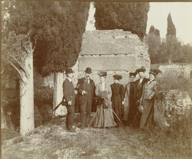 Groepsportret van vijf vrouwen (van wie één achter een camera) en twee mannen voor een ruïne in Italië of Frankrijk