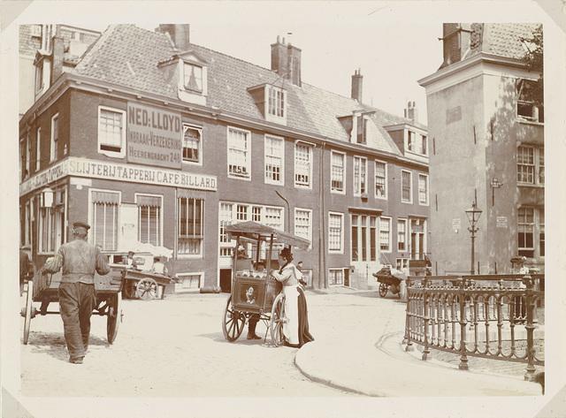 Verkoopster en een man met een handkar op de hoek van de Lijnbaansgracht en de Spiegelgracht