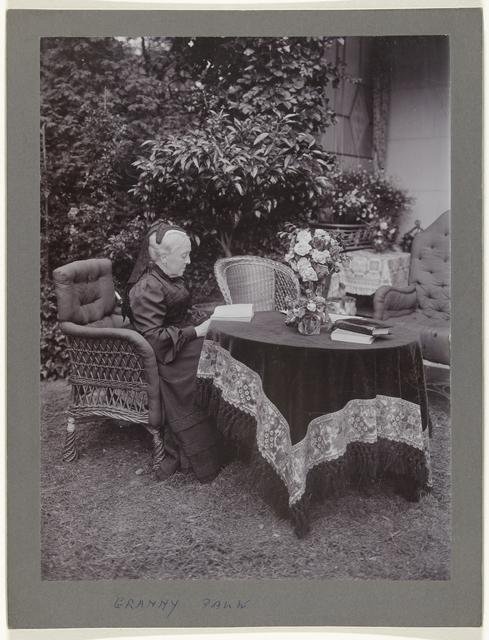 Aletta Cornelia Anna Voombergh (1828-1913), moeder van de fotograaf, lezend aan een tafel achter het huis