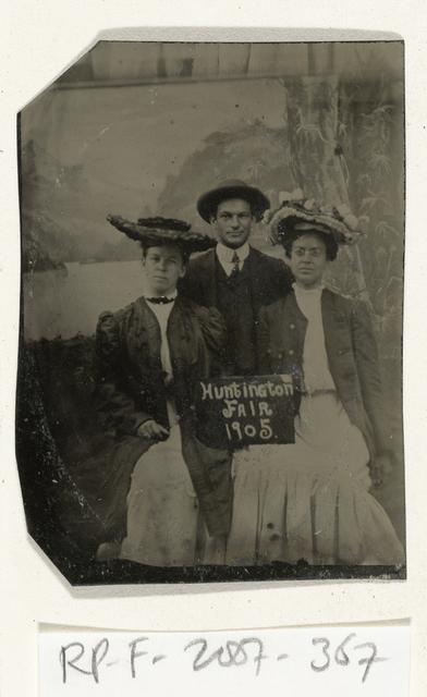 Portret van een man en twee vrouwen voor een geschilderd achtergronddoek (boom, meer en bergen) en een bordje met de tekst 'Huntington FAIR 1905'
