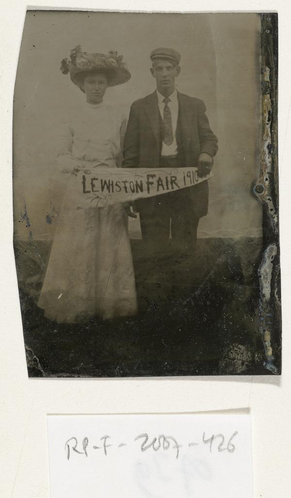 Portret van een man en vrouw, die een doek vasthouden met de tekst LEWISTON FAIR 1910