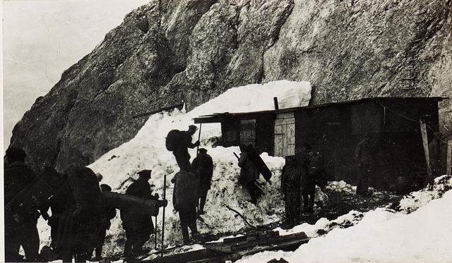 """Russische Gefangene übernehmen auf der Dodici Südspitze Baumaterial, um es durch den 2km langen Eisstollen auf die """"S"""" - Stellung zu tragen."""
