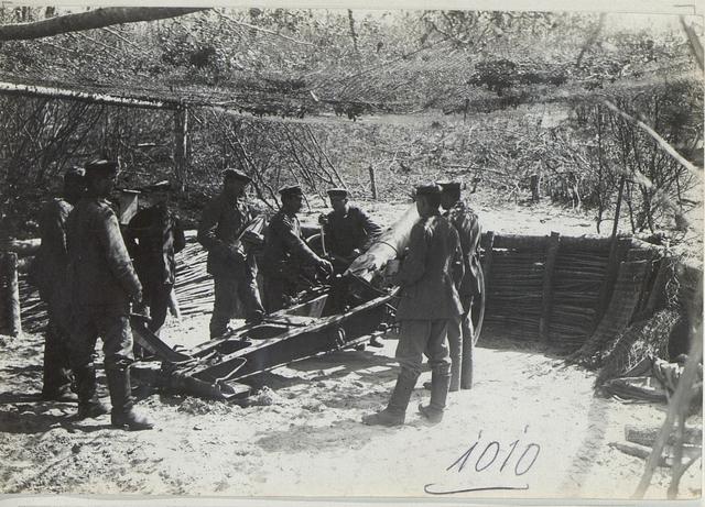 Zur Maskierung mit Drahtnetz überspannte deutsche schwere 15 cm Haubitzen beim ottom.Korps.