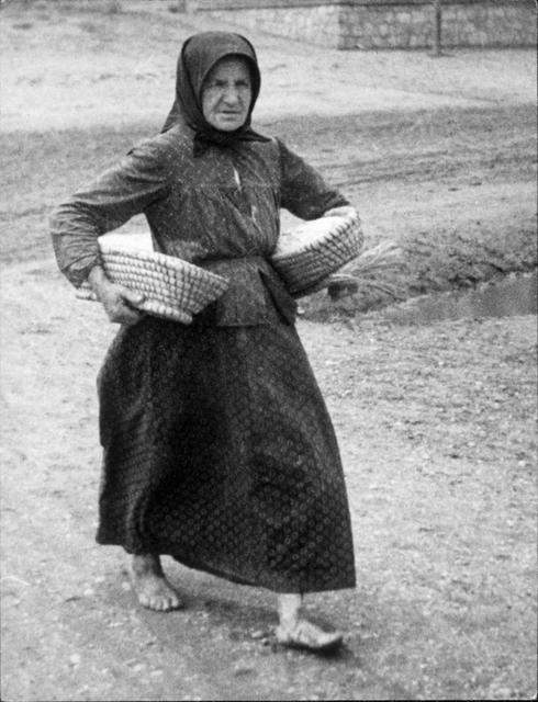 Burgenland: Frau mit zwei Brotsimperln unter dem Arm, barfuß, Bäuerin
