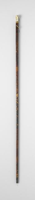 Dunne stok (badine) van hout belijmd met schildpad en voorzien van een knop van wit porseleinen, versierd met ornamentjes van bladgoud, gezet in een vergulde rand