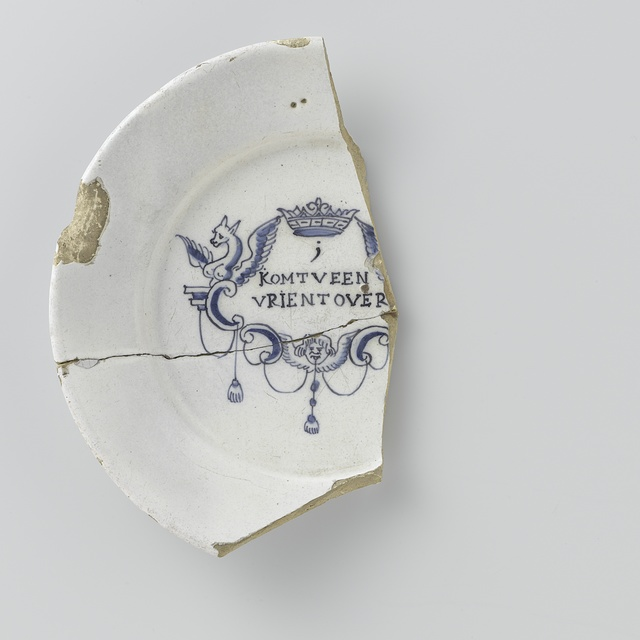 Fragment van een bord, beschilderd in blauw onder het glazuur met een cartouche, waarin de tekst: i // KOMT V EEN // VRIENT OVER