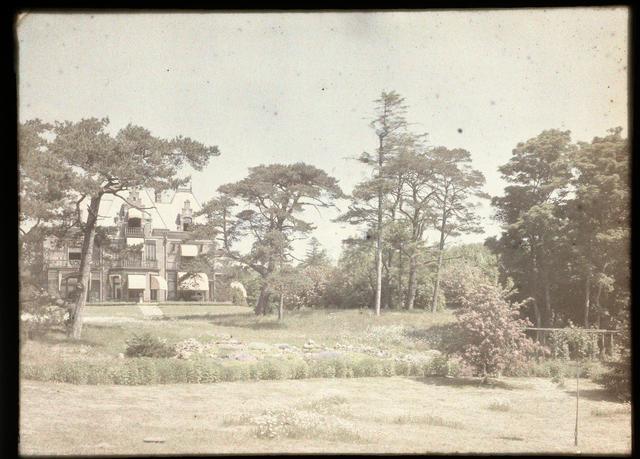 Gezicht op een landhuis (linksachter) met op de voorgrond een park of tuin met bomen