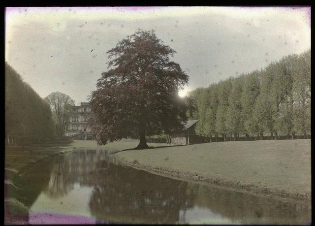 Gezicht op een landhuis, met op de voorgrond een zichtkanaal (?) en een boom