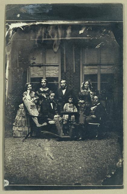 Groepsportret van de families Asser en Oppenheim in een tuin