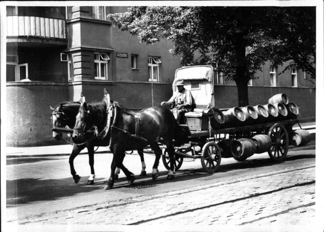 Hölzener Bierwagen mit Fässern wird von einem Pferdegespann gezogen