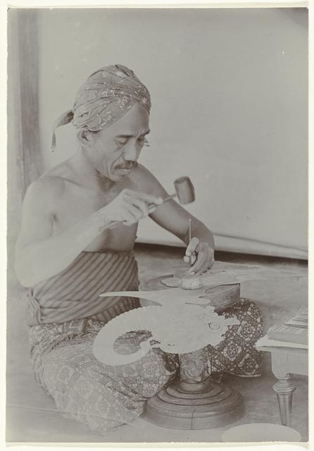 Javaanse man maakt met hamer en instrumenten een afbeelding gelijkend een menselijk gestalte