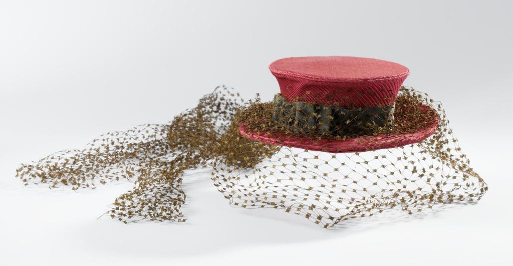 Kleine hoed van doorgestikte rode ripszijde met platte bol en licht opstaande rand, versierd met bruin grosgrain en bruine voile