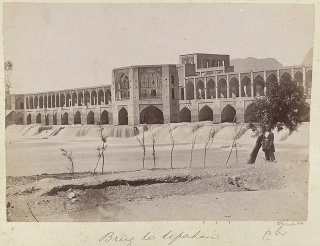 Perzië, man bij waterval en brug te Isfahan