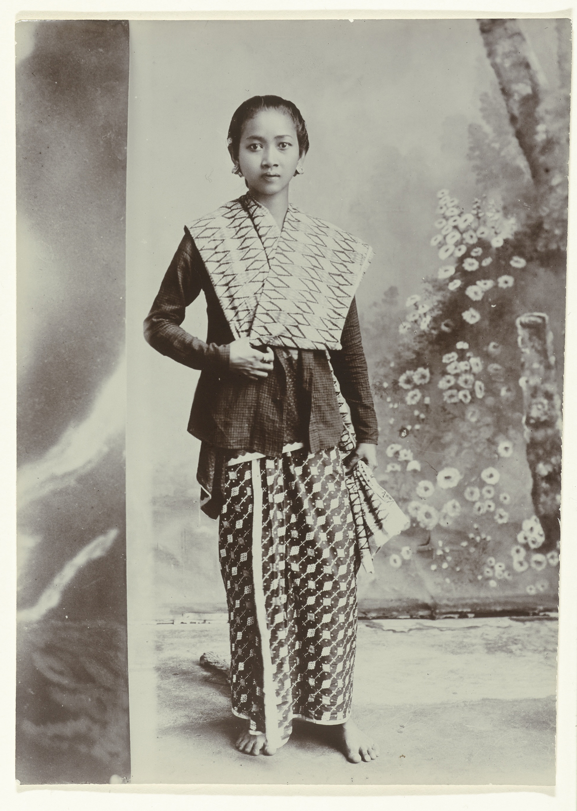 71396b4519d79f Studioportret van een jonge Javaanse vrouw in een sarong met batik motief  en een overhemd met