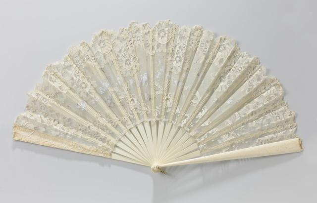 Vouwwaaier met blad van blond machinaal kant, waarin organza tussenzetsel beschilderd met tempera in grisaille met vogels op bloesemtak, op een montuur van been