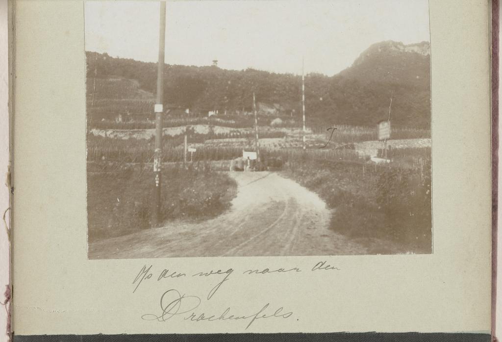 Zandweg met een spoorwegovergang in een berglandschap nabij Konigswinter