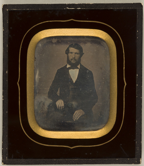 Portrait of a bearded man, seated, resting his right arm on a table.