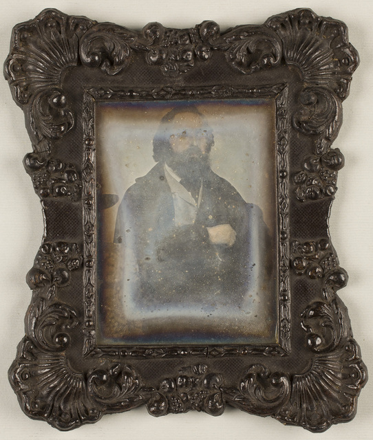 Portrait of a bearded man, wearing a coat, seated. A tablecloth decorated with ornamental motif is visible on the left, in the foreground.