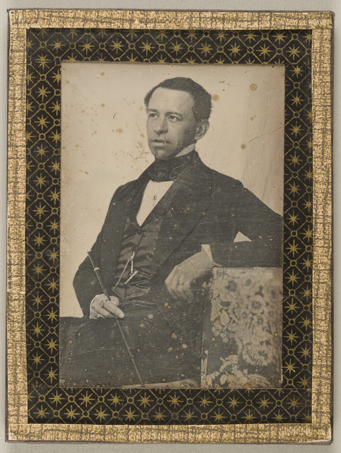 Portrait of a man with a stick, seated, resting his left arm on a chair