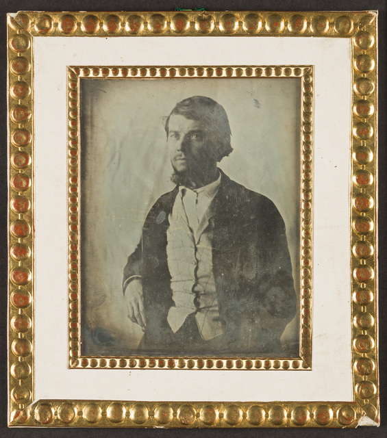Portrait of a man with beard, seated, wearing suit and checked waistcoat