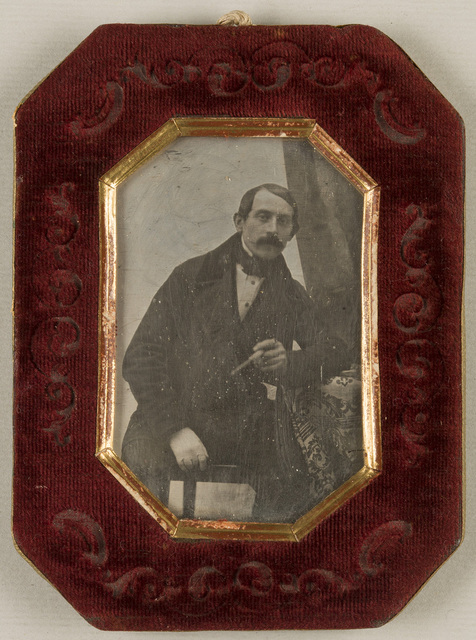 Portrait of a man with moustache, seated, resting his left arm on a table, holding a cigar. His right hand in glove is lying in his lap. The tablecloth is decorated with floral motif. At the upper right corner is hanging drapery.