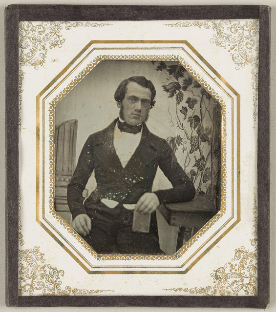 Portrait of a man with side-whiskers, in a tailcoat, seated, resting his left arm on a wooden table. In tha background visible painted decoration comprised by a column on the left and a vine on the right.