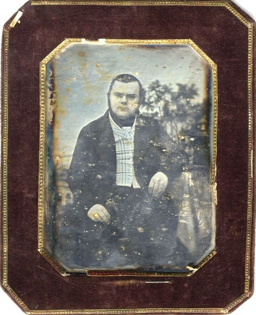 Portrait of a thickset man, seated, resting his left arm on a table. The tablecloth is decorated with ornamental motif. Trees and architecture visible in the background (studio decoration?)