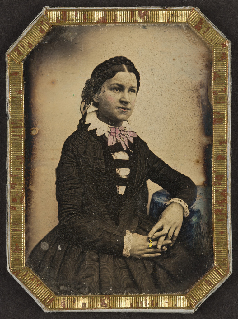 Portrait of a woman, seated, resting her left arm on a table. Her dress and face are richly coloured.