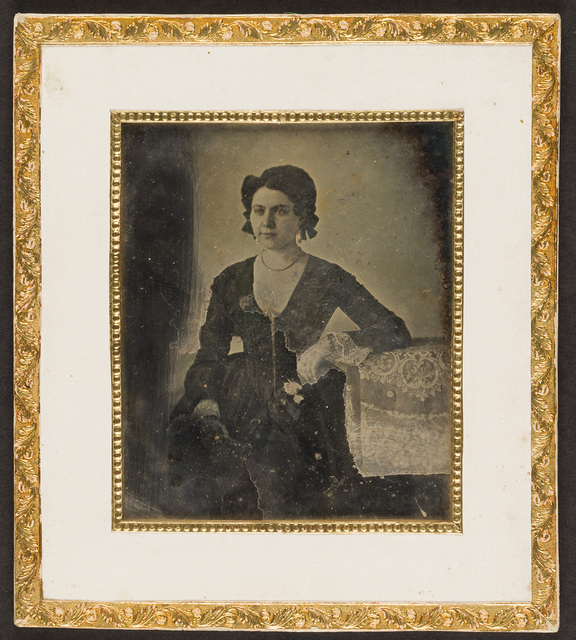 Portrait of a woman, seated, resting her left arm on a table. The image right side is veiled by foreign coating.