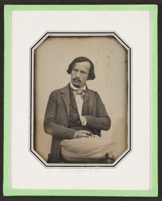 Portrait of Czech painter Bedrich Havranek (Bedřich Havránek), seated, looking to the left, crossing his legs.