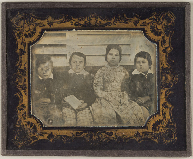 Portrait of four children, sitting in front of a wooden wall (?)
