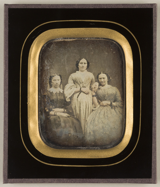 Portrait of three women in long dresses of the mid-19th century. The one in the middle is standing, the other two are sitting.